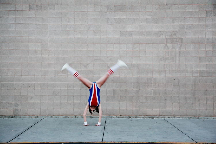 Woman In Old-Fashioned Sports Costume Doing Cartwheel On Sidewalk Against Wall