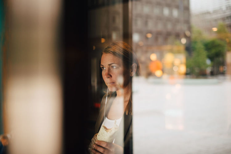 Portrait of woman looking away in city