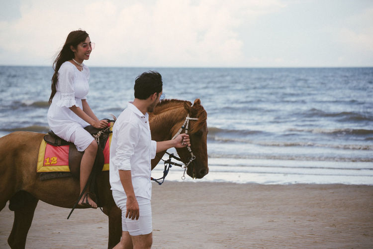 Young woman with boyfriend riding horse at beach