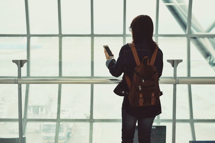 Rear View Of Woman Using Smart Phone While Standing On Window