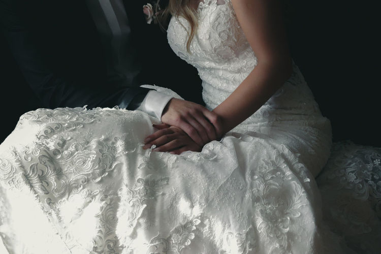 Midsection of newlywed couple holding hands