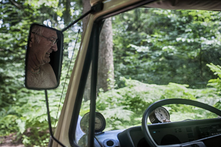 Reflection Of Smiling Senior Man On Side-View Car Mirror In Forest