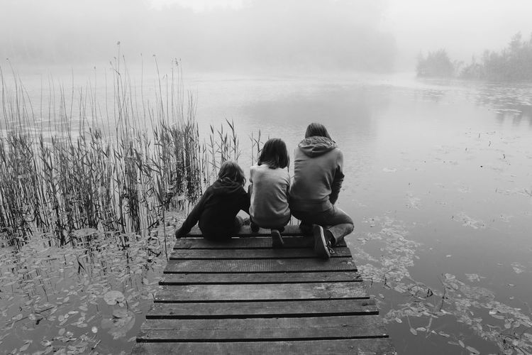 Adult Bonding Childhood Day Family Friendship Human Body Part Lake Leisure Activity Lifestyles Men Nature Outdoors People Real People Rear View Sitting Sky Togetherness Two People Water Women