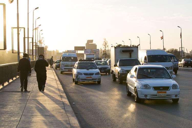 Egyptian policemen walking on the 6th October bridge in central Cairo at dusk Africa Cairo Car City City Life Crowded Day Egypt Mode Of Transport Near East North Africa Outdoors People Police Policeman Real People Road Street Sunlight Sunset Traffic Traffic Jam Transportation Transportation Urban