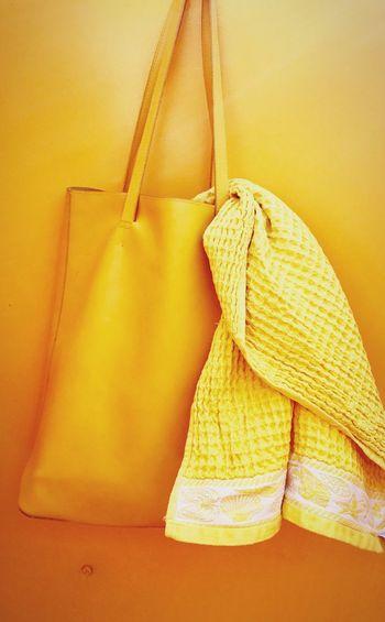 Towel in bag hanging on orange wall