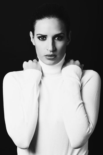 Young brunette woman wearing white poloneck. Attractive girl, model of fashion in black and white. Studio shot on black background. Adult Beautiful Woman Beauty Black Background Front View Hairstyle Indoors  Isolated Lifestyles Looking At Camera Make-up One Person Portrait Real People Standing Studio Shot Waist Up Women Young Adult Young Women