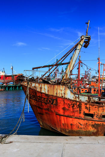 Fishing boat moored at harbor against blue sky