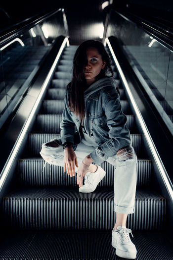 Full length portrait of young woman on escalator