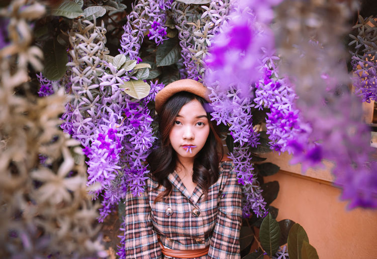 Portrait of beautiful young woman standing against purple flowering plants