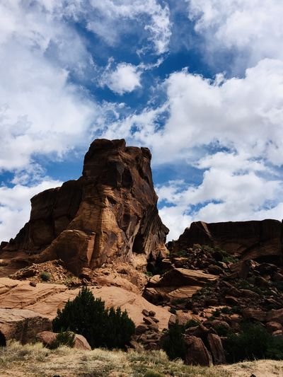 Red rock formations on landscape against cloudy sky
