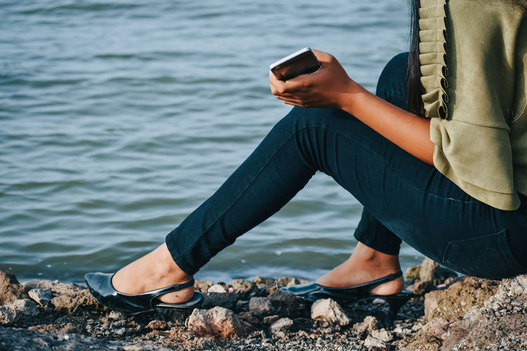 Low section of woman holding mobile phone while sitting by sea
