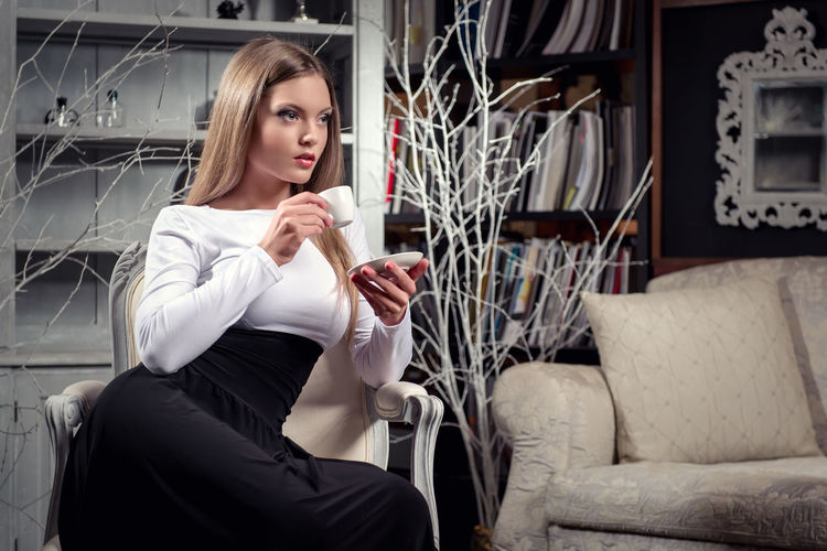 Woman Having Drink While Sitting On Chair At Home
