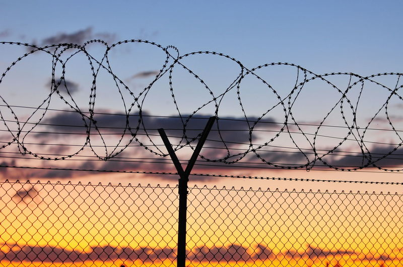 Barbed wire against sky during sunset