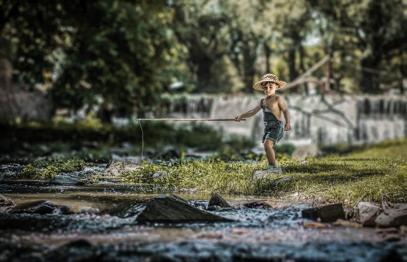 Boy holding stick by stream on field
