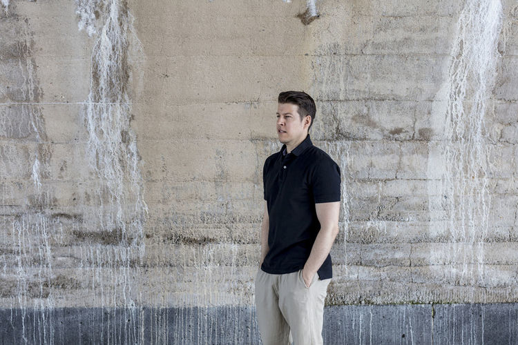 Casually dressed man, wearing khaki pants and a golf shirt posing for the camera behind a wall. Long shot. Profile. Adult Khaki Pants Man Profile Standing Wall Casual Clothing Caucasian Day Daylight Golf Shirt Good Looking Hairstyel Hands In Pockets Handsome Male Model Pose Posing Relaxed Summer Tall Urban Warm