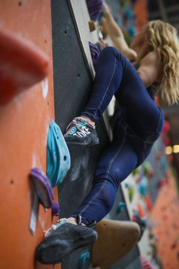 Low Angle View Of Female Athlete Climbing Wall