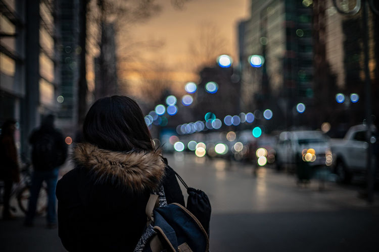 Rear view of woman standing on street in city at night