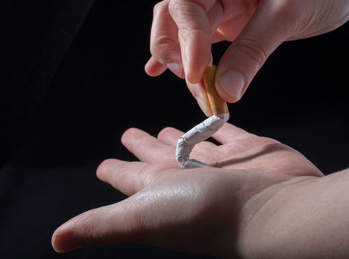 Close-up of hands crushing cigarette over black background