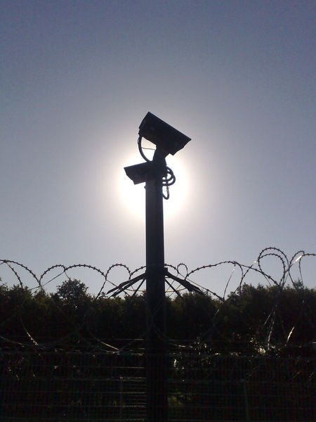 Cctv No Filters  Silouette Camera Sunlight Surveillance Spying Shadow Barbed Wire Big Brother Is Watching You Big Brother - Orwellian Concept CCTVTower Cctv Camera With Sun Behind