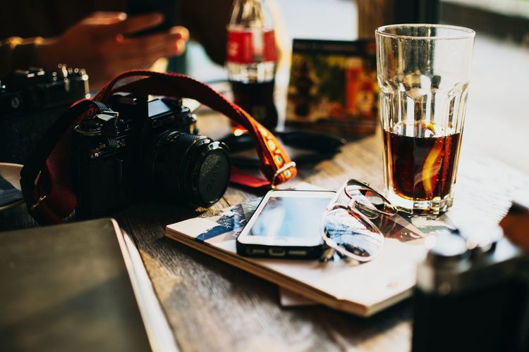 High angle view of mobile phone with camera and drink on table