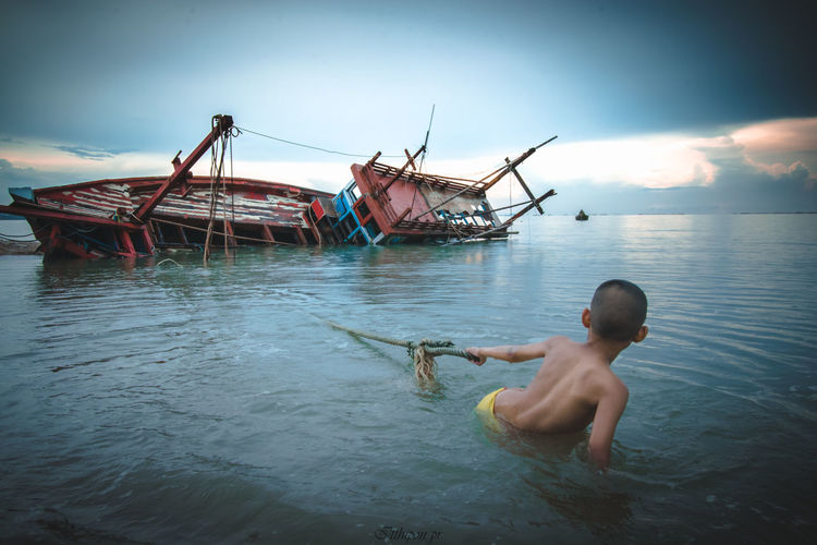 Boys Child Childhood Day Lifestyles Males  Men Mode Of Transportation Nature Nautical Vessel One Person Outdoors Real People Sea Shirtless Sky Transportation Water Waterfront