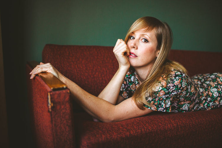 Woman looking away while sitting on sofa
