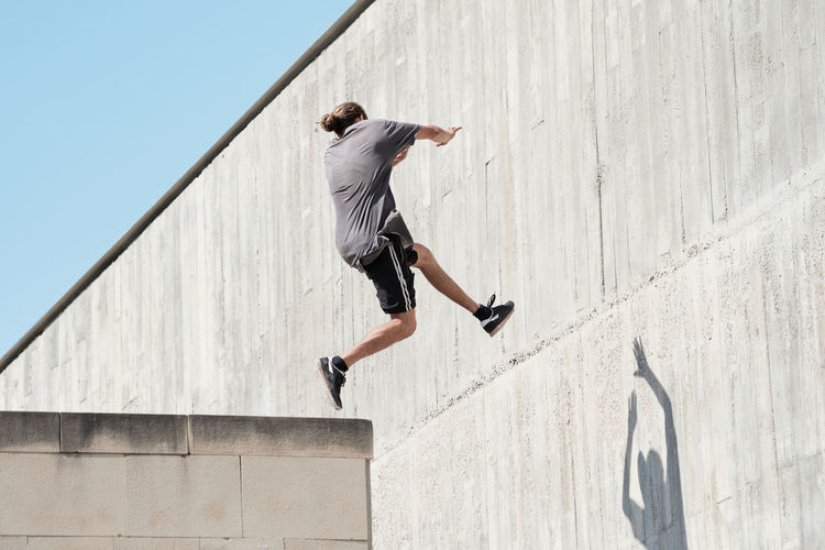Full length rear view of man jumping against wall