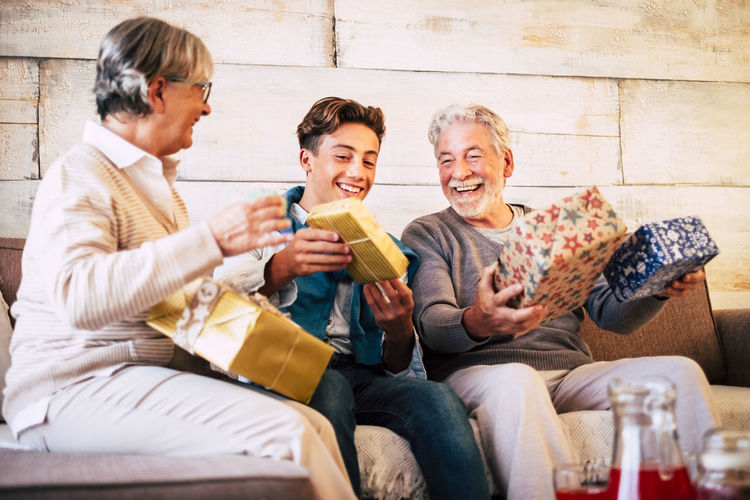Smiling grandparents giving gift to grandson at home