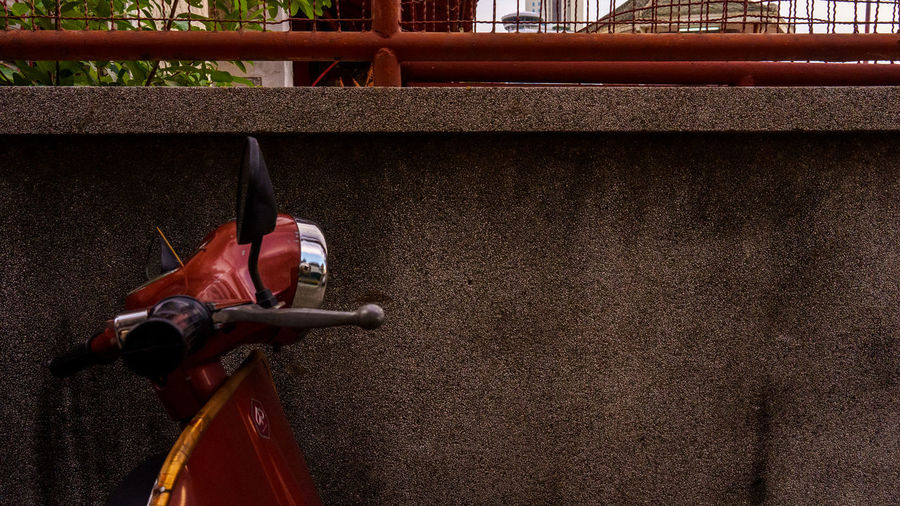Close-up of bicycle parked against wall
