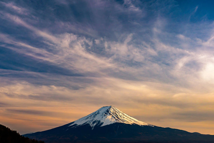 Scenic view of snowcapped volcano against sky during sunset