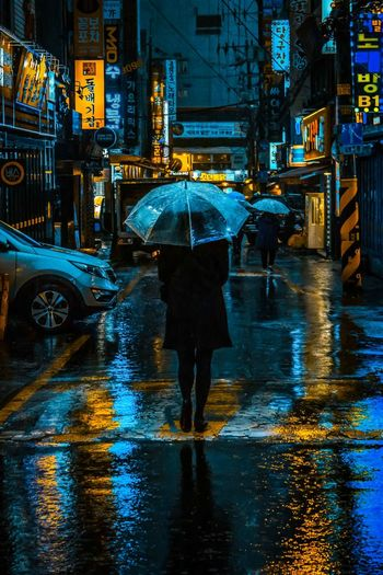 Rear View Of Woman With Umbrella Walking On Illuminated Street During Rainy Season