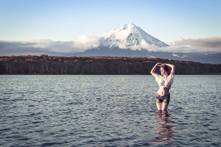Woman standing in river against snowcapped mountain