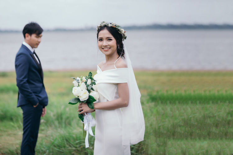 Young couple standing by railing on land