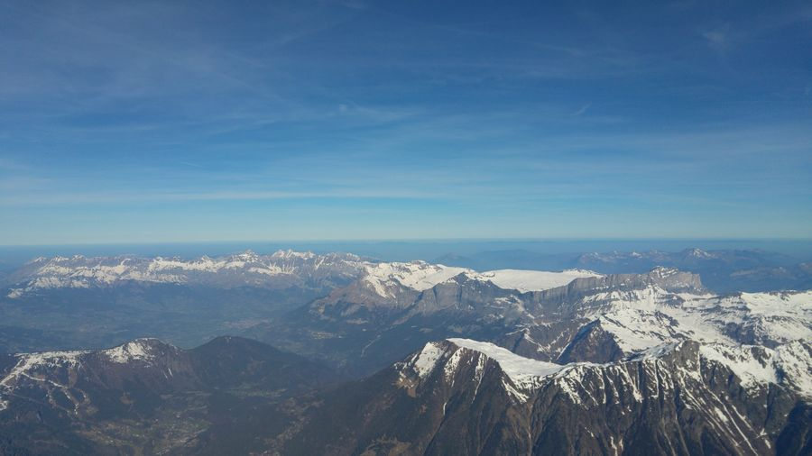 Aerial view of snowcapped mountains against blue sky