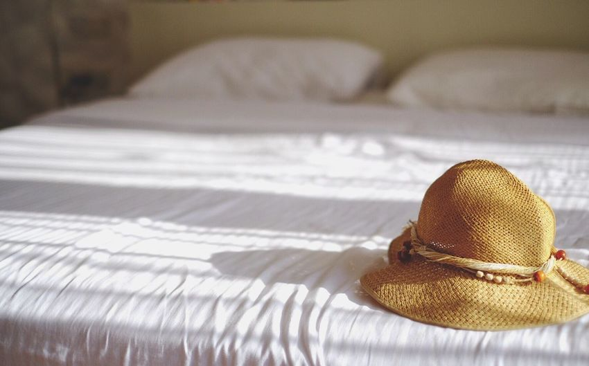 Hat on bed during sunny day