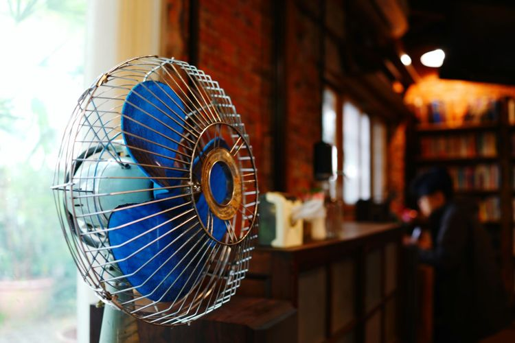 Close-up of electric fan against window at restaurant
