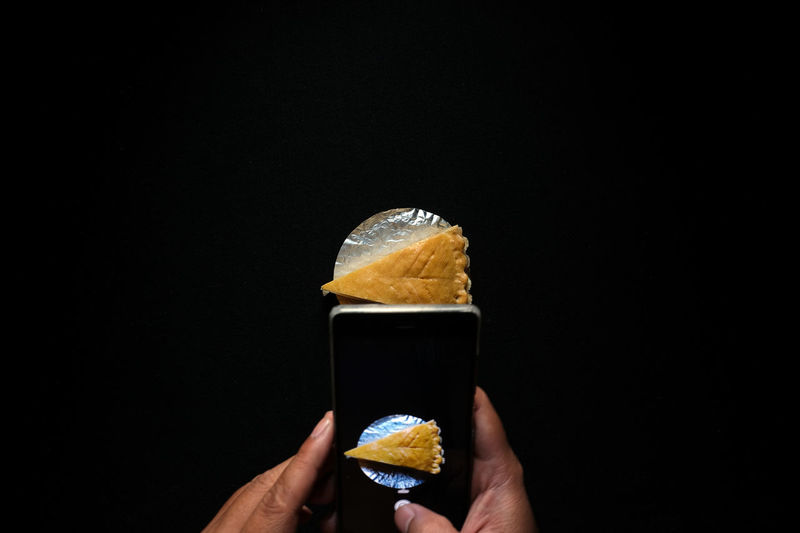 Midsection of person holding ice cream against black background