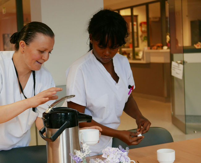 Caretakers with coffee maker in nursing home
