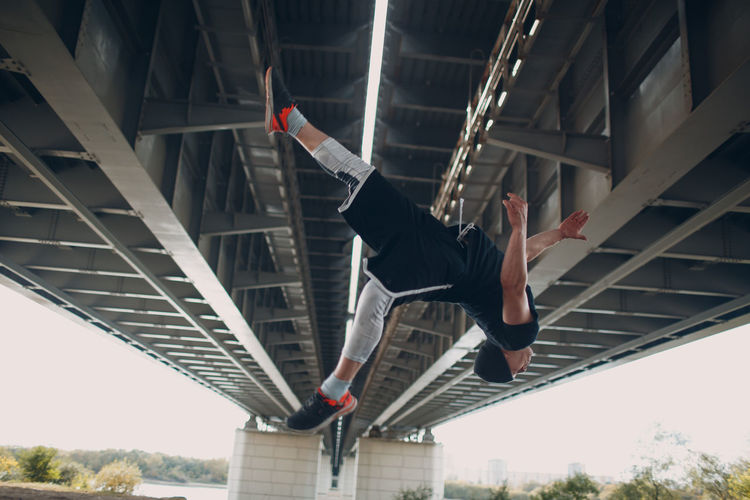 Low angle view of man jumping on bridge