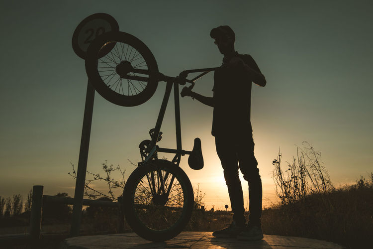 Silhouette man standing by bicycle against sky during sunset