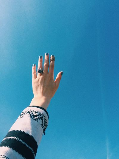 Cropped hand of woman gesturing against clear blue sky