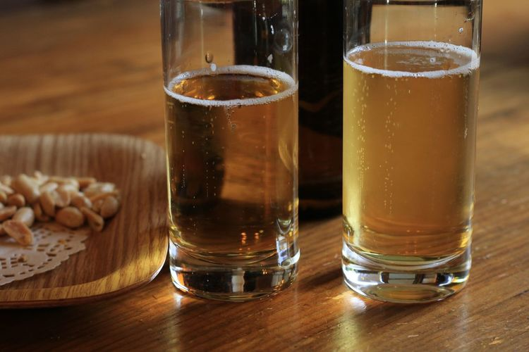 Close-up of beer glasses by peanut in plate on table