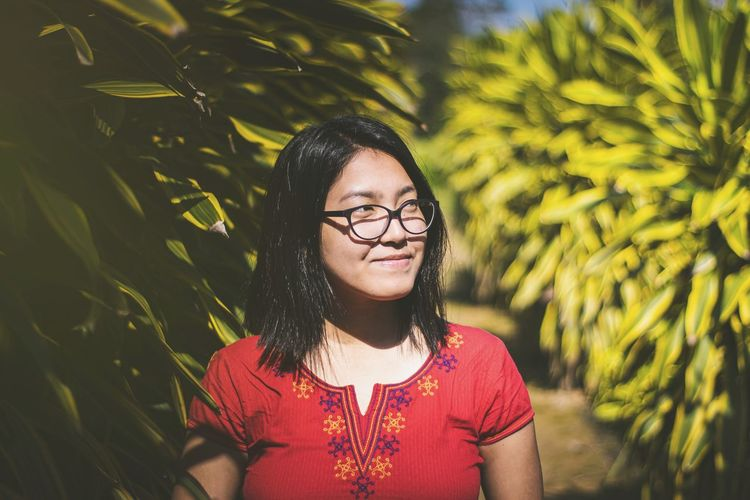 Close-up of smiling young woman looking away by plants