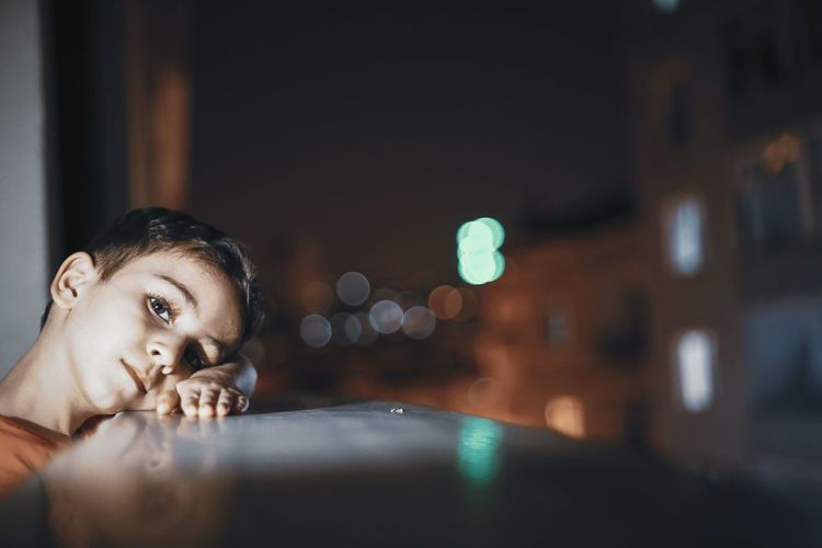Portrait of boy leaning on window sill at night