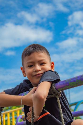 Portrait of cute boy by railing against sky