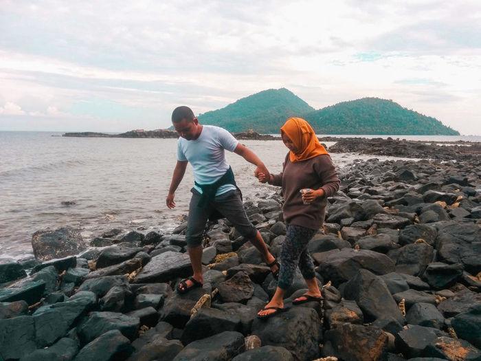 Full length of rocks on beach against sky