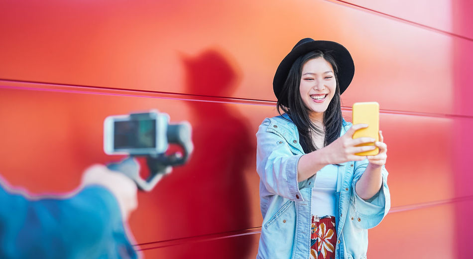 Cropped hand of person holding camera with woman taking selfie with mobile phone