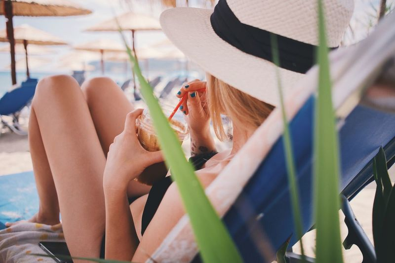 Woman drinking coffee while relaxing on lounge chair at beach