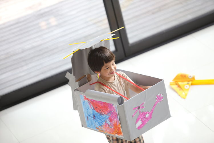 Boy In Helicopter Made With Box Standing On Floor