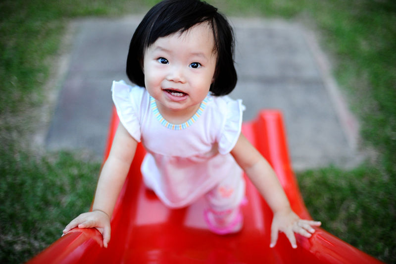 High Angle View Of Cute Girl Playing On Red Slide At Playground